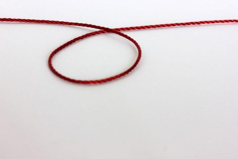 амулет из красной веревочки на запястье
